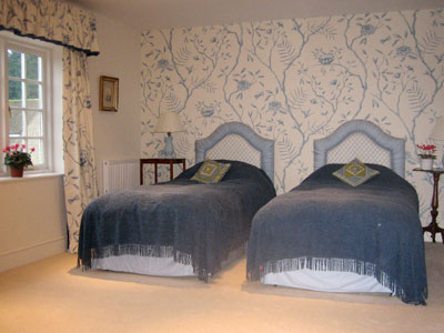 Image of two single beds with blue covers